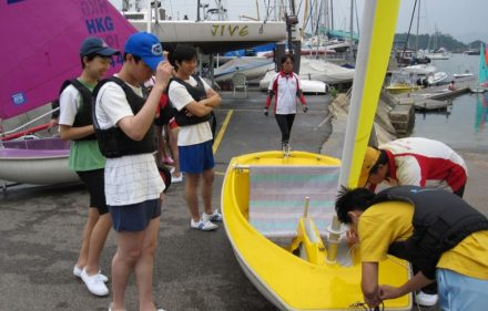young people getting a boat ready to go sailing in hong kong