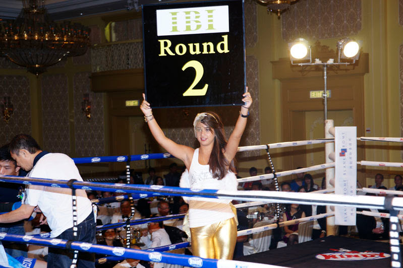 woman on a boxing ring holding a sign with the ibi sponsor